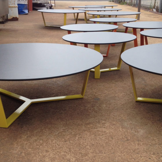 Fleur coffee table in setting with yellow powdercoated base and black round table top