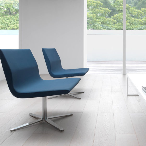 Camilla lounge chair. Fully-upholstered teal blue shell on swivel base