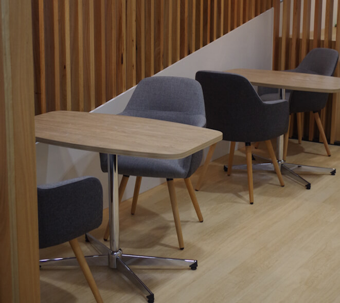 Casual setting with timber batten screens as backdrop, Struve upholstered meeting Chairs and boat-shaped meeting tables.