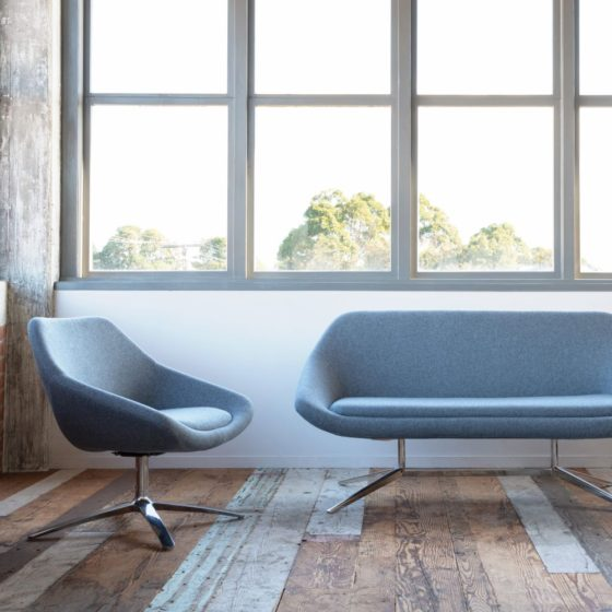 Skann chair and lounge both upholstered in grey, in a setting